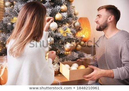 happy couple decorating christmas tree at home stock photo © dolgachov