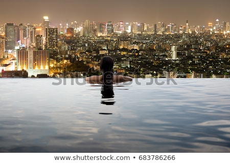 Young woman in outdoor swimming pool with city view at night Stock photo © galitskaya