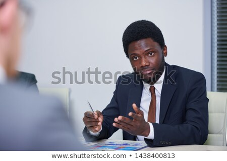 Young African economist in formalwear discussing working points Stock photo © pressmaster