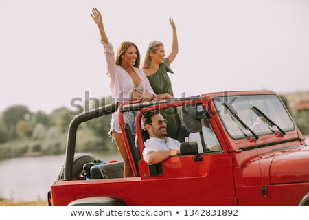 Stock photo: Young people having fun in convertible car by river