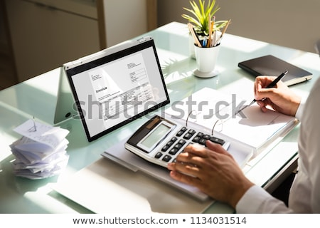 businessmans hands working on invoice on laptop stock photo © andreypopov
