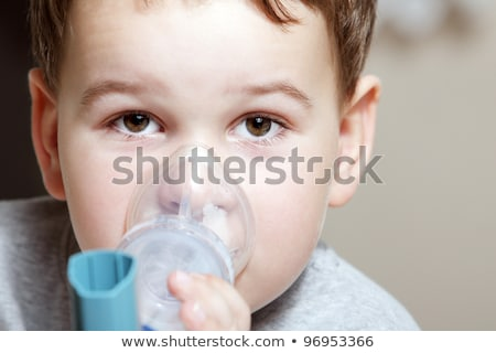Stock photo: Close-up image little boy using inhaler for asthma.
