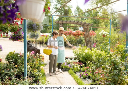 mature gardener in hat and apron showing white flowers to one of clients stock photo © pressmaster