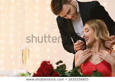 happy man puts necklace on his girlfriend Stock photo © dolgachov