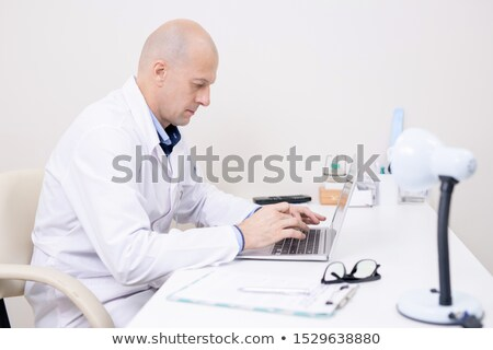 Serious middle aged doctor in whitecoat concentrating on laptop work Stock photo © pressmaster