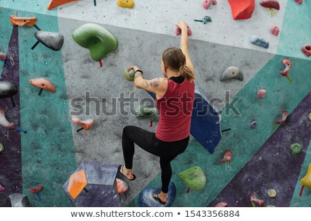 Rear view of young sportswoman grabbing by small rocks on climbing wall Stock photo © pressmaster