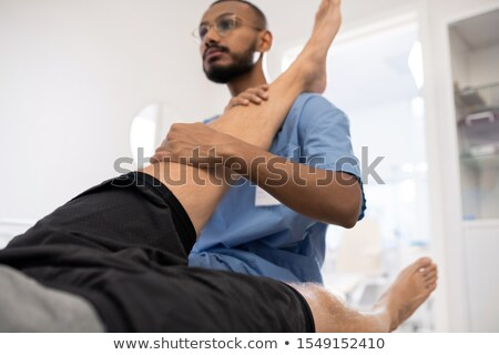 Qualified medical professional massaging sick knee of patient in hospital Stock photo © pressmaster