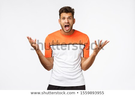 Disappointed handsome bearded masculine man, raise hands sideways in dismay, gasping shocked, stare  Stock photo © benzoix
