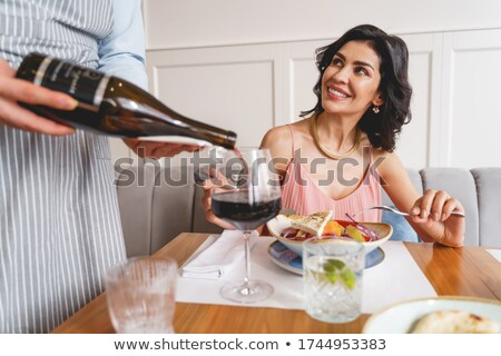 Young man pouring wine into wineglass while sitting by served table Stock photo © pressmaster