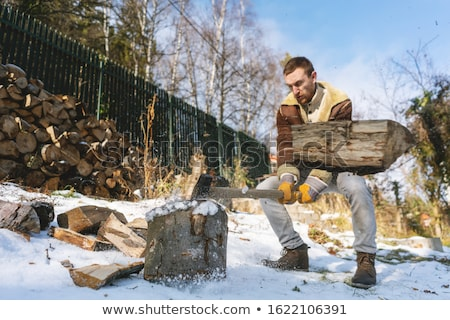 Man chopping wood with an axe, pieces and debris flying around Stock photo © Kzenon