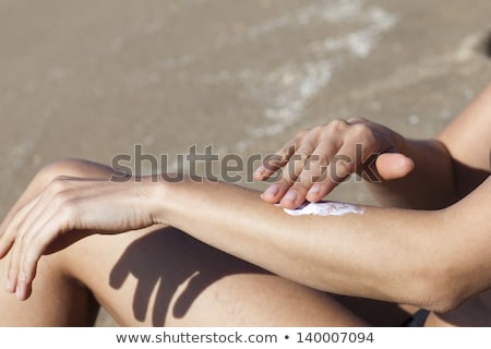woman sunburn putting some lotion on  Stock photo © dacasdo