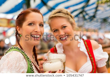 Stock photo: two bavarian girls cheering with beer