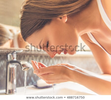 Woman in a bathroom, washing her hands in front of a mirror Stock photo © photography33