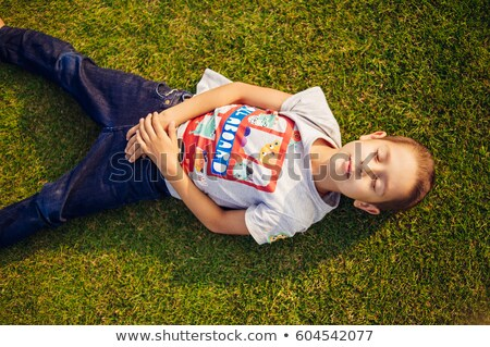 playful young couple laying down in a green grass field stock photo © get4net