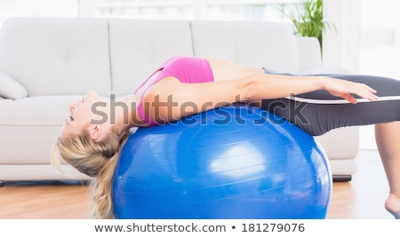 pretty blonde woman stretching in the living room in her appartment stock photo © wavebreak_media