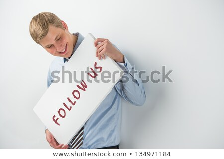 Handsome businessman showing 'follow us' text on a billboard Stock photo © HASLOO