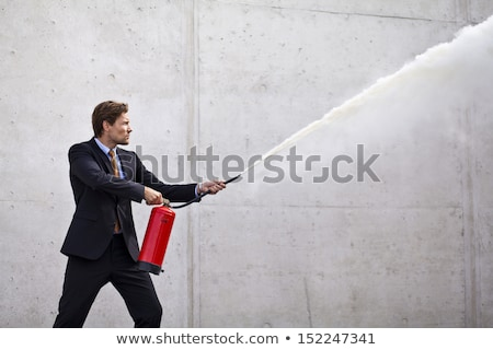 Focused businessman using a fire extinguisher Stock photo © Rugdal