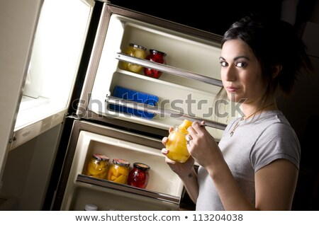 Young woman snacking from her refrigerator Stock photo © dash
