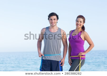 happy athletic couple   man and woman with measuring tape on and stock photo © vlad_star