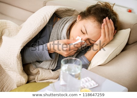Stock photo: Young sick woman in blanket with thermometer