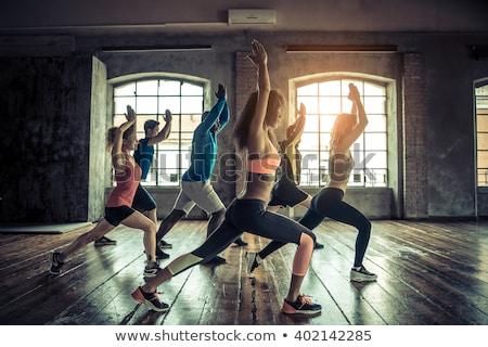 Beautiful cheerful sportswoman training in gym  Stock photo © deandrobot