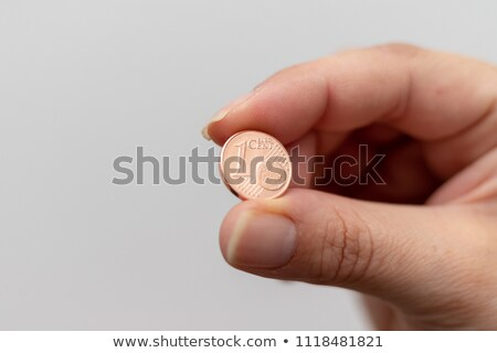 Business woman holding one euro coin between fingers Stock photo © stevanovicigor