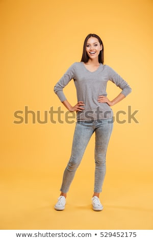 Happy casual woman in sweater standing with hands on hips Stock photo © deandrobot