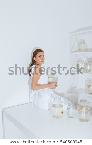 cute young woman sitting and holding gold with in jar stock photo © deandrobot