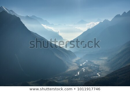 Majestic view of silhouettes of mountains and low clouds at sunset Stock photo © denbelitsky
