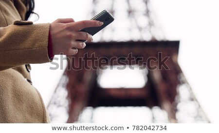 Stock photo: Lady looking for taxi number in smartphone app and calling to book vehicle