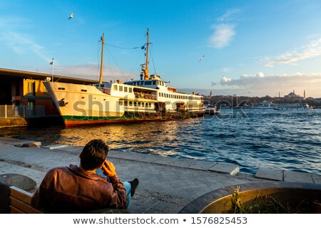 Man sitting on jetty speaking on phone Stock photo © IS2