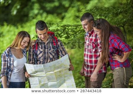 Quattro persone parco guardando mappa comunicazione recinzione Foto d'archivio © IS2
