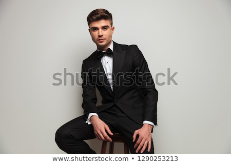 elegant young man in tuxedo sits on wooden chair Stock photo © feedough