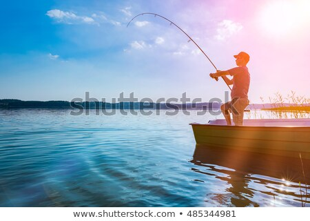 fishing fisherman with rod on boat and on shore stock photo © robuart