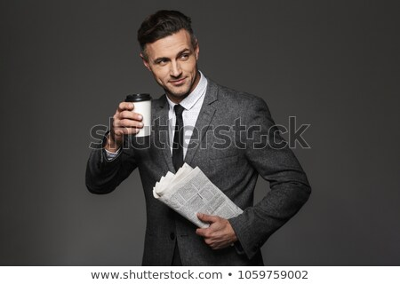 Image of adult man 30s in businesslike suit drinking coffee from Stock photo © deandrobot