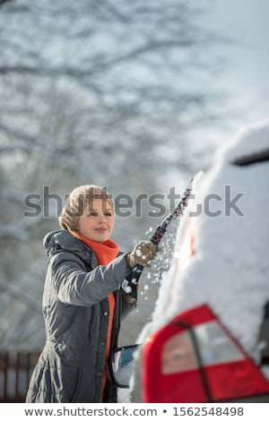 Pretty, young woman cleaning her car from snow after heavy snowstorm Stock photo © lightpoet