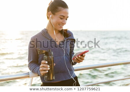 Sports woman standing on the beach listening music holding water chatting by phone. Stock photo © deandrobot