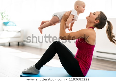 A Portrait of beautiful young mother in sports wear with her charming little baby in training sessio imagine de stoc © Lopolo