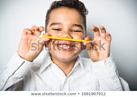 Black boy holding school pensil and take it on his nose Stock photo © Lopolo