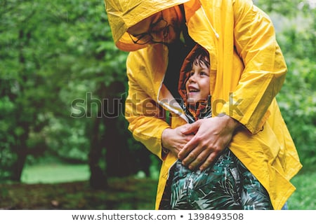 family with childs walk on rainy day with raincoat stock photo © lopolo
