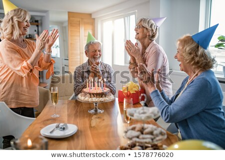 Senior friends clapping hands to their friend with birthday cake Stock photo © pressmaster