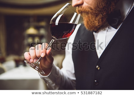 Serious male sommelier smelling red wine from wineglass Stock photo © pressmaster