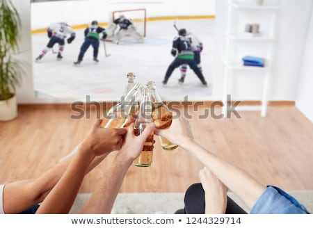 friends watching ice hockey on projector screen stock photo © dolgachov