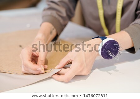Hands of young seamstress pinning cut sketch to textile Stock photo © pressmaster