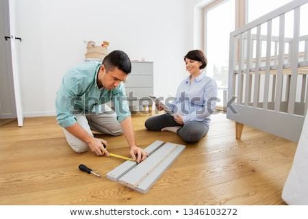 father with manual assembling baby bed at home Stock photo © dolgachov