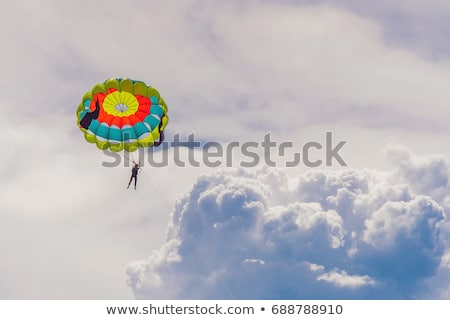 Fiatal nő ejtőernyő felhők nő égbolt víz Stock fotó © galitskaya