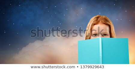 red haired girl behind book over starry night sky Stock photo © dolgachov