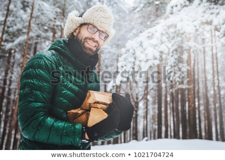 Outdoor shot of smiling glad male with beard and mustache wears spectacles, anork and warm hat, hold Stock photo © vkstudio