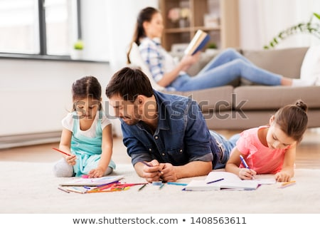 father with little daughters drawing at home Stock photo © dolgachov