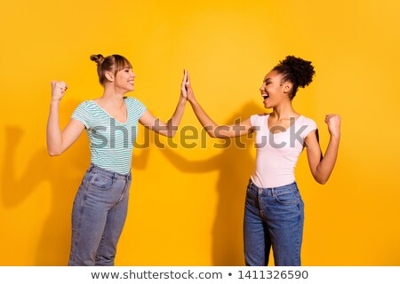 Image of delighted multinational women smiling and screaming together Stock photo © deandrobot